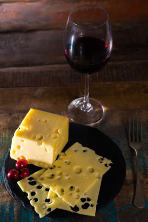 Dessert with medium-hard mild Swiss cheese Emmental and glass red wine served on round black stone