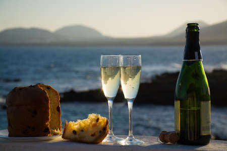 Sweet fruit Chrismas and New Year cake panettone with two glasses with champagne served outside with blue sea background