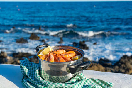 Fishermen village, fresh cooked prawns, shrimps in steel pan served outside with lemon, sea view