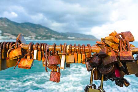 Love padlocks or love locks on a bridge in the harbor of Cefalu on blurred sunlight sea background