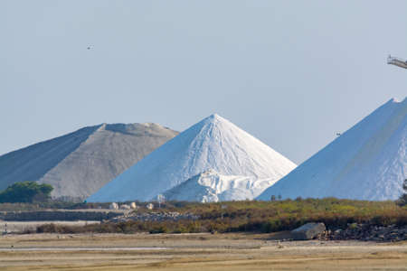 Salt works, industrial plant with white piles of Camagrue sea salt, ready for packaging