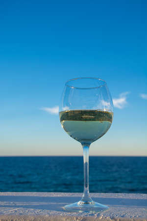 One glass of cold white wine served on outdoor terrace with beautiful romantic  sea view Stock Photo