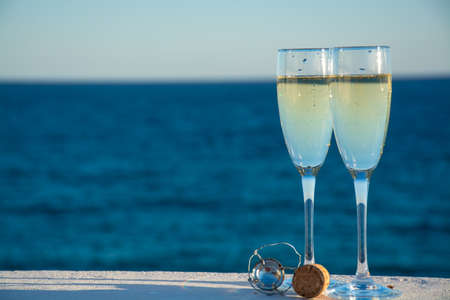 Two glasses with champain or cava sparkling wine served outside on terrace, luxury resort with sea view, romantic vacation Archivio Fotografico