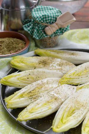Salade de chicorée amère belge fraîche fraîche prête à cuire avec des herbes et de l'huile d'olive, Close up