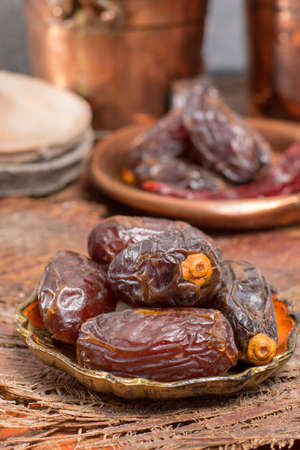 Traditional Middle East dessert, healthy food, big medjool dates fruits served on old wooden table