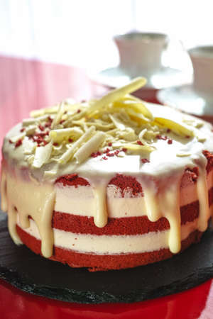 Classic American dessert red velvet cake is traditionally a red, chocolate layer cake, layered with white cream cheese or ermine icing