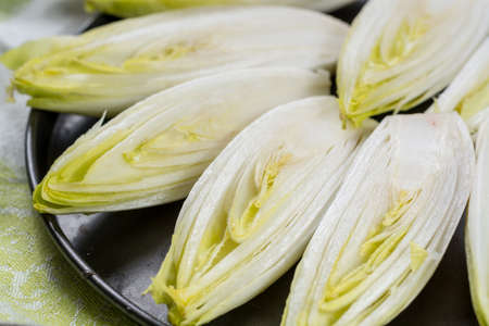 Fresh raw Belgian bitter chicory salad ready to cook, close up