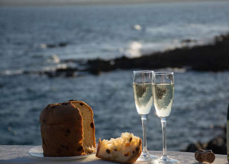 Sweet fruit Easter cake panettone served with two glasses with champagne outside with beautiful romantic sea view
