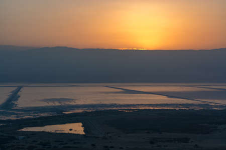 Sunrise over lowest salty lake in world below sea level Dead sea, full of minerals near luxury vacation resort Ein Bokek, perfect place for medical treatments, climatotherapy, thalassotherapy and heliotherapy. Stockfoto