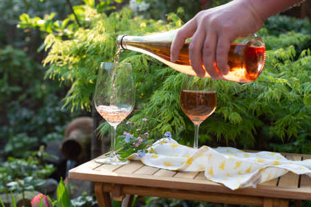 Waiter pouring cold orange wine in glasses on outdoor terrace in garden in sunny day