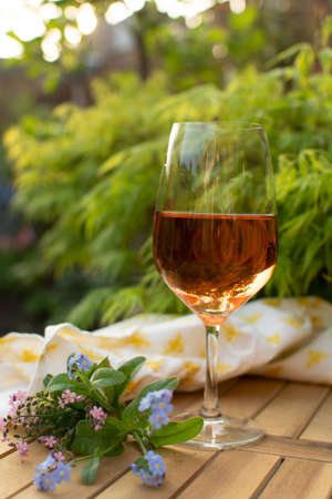 Orange wine glass served on outdoor terrace in garden with flowers