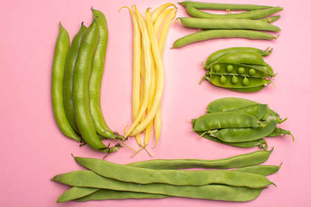 Flat lay food concept with fresh legumes,  green ripe bread beans, garden beans, sugar snaps, sweet peas, peas and yellow butter beans copy space close up isolated on pink background Foto de archivo