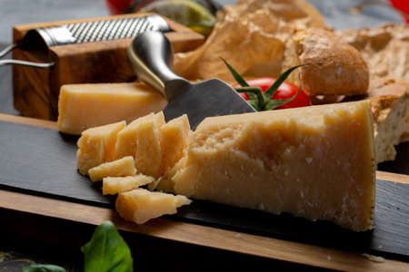 Traditional italian food - aged Italian parmesan hard cheese Parmigiano-Reggiano with cheese knife, tomato, basil, olive oil