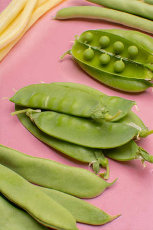 Flat lay food concept with fresh legumes,  green ripe bread beans, garden beans, sugar snaps, sweet peas, peas and yellow butter beans copy space close up isolated on pink background Фото со стока