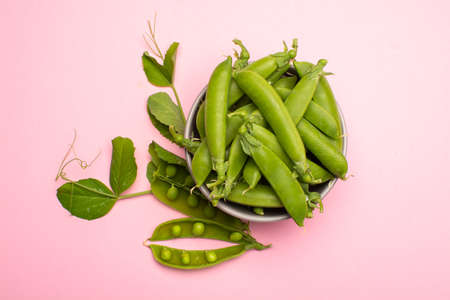 Fresh green ripe sugar snaps, sweet peas in bowl copy space close up on light pink background
