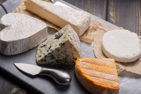 French cheeses plate in assortment, blue cheese, brie, munster, soft goat cheese, Neufchatel heart shaped cheese