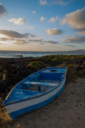 Sunset over the sea landscape with old blue wooden fishing boat 免版税图像