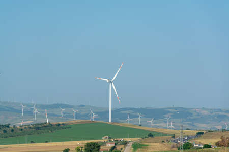 Modern wind farm with big wind turbines towers, source for renewable green energy Stock Photo