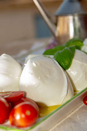 Fresh soft Italian white cheese mozzarella buffalo, original from Campania, Paestrum and Foggia regions, South Italy, served with tomatoes and fresh basil