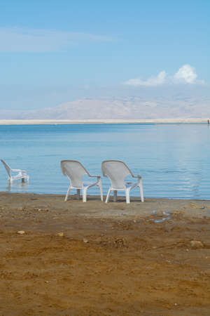 Chairs on beach, lowest salty lake in world below sea level Dead sea, full of minerals near luxury vacation resort Ein Bokek, perfect place for medical treatments, climatotherapy, thalassotherapy and heliotherapy.