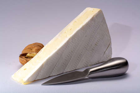 Piece of french soft-ripened white mold cow milk cheese brie produced in Seine-et-Marne region, France, isolated on white 스톡 콘텐츠