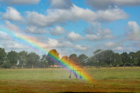 Ð¡atastrophic drought and heat in Europe, nature disaster, irrigation of grass fields and colorful water rainbow in North Brabant, Netherlands Stock Photo