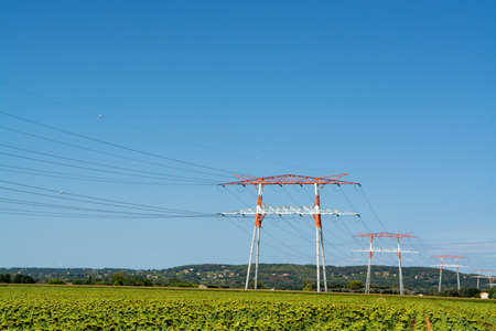 Landscape with high voltage power line, sunflowers field and blue sky
