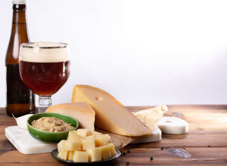 finger food usually served with glass of beer, cubes hard old Dutch cow and goat cheese with Dijon mustard