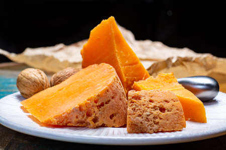 Pieces of native French aged cheese Mimolette, produced in Lille with greyish curst made by special cheese mites close up Stock Photo