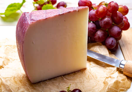 Traditional Spanish cheese, one piece of Murcian wine cheese from goat milk with rind washed in red wine, served with fresh ripe grapes Foto de archivo - 108077308