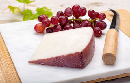 Traditional Spanish cheese, one piece of Murcian wine cheese from goat milk with rind washed in red wine, served with fresh ripe grapes Standard-Bild