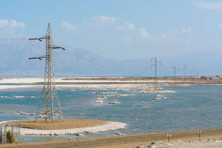 Power line above lowest salty lake in world below sea level Dead sea, full of minerals near luxury vacation resort Ein Bokek, perfect place for medical treatments, climatotherapy, thalassotherapy and heliotherapy.