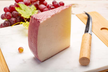 Traditional Spanish cheese, one piece of Murcian wine cheese from goat milk with rind washed in red wine, served with fresh ripe grapes Foto de archivo - 108866648