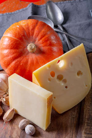 Ingrediens for traditional seasonal Swiss dish, pumpkin fondue with gruyer and emmentaler cheeses, fresh creme and nutmeg close up Stock Photo