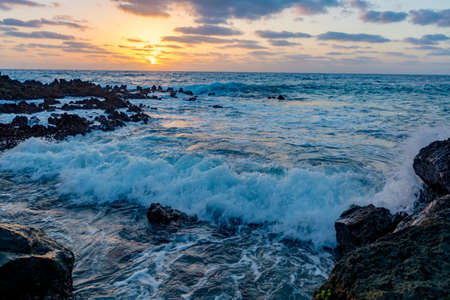 Dramatic ocean view , seascape, sun's rays pass through  clouds at sunrise, black volcanic coastline on Lanzarote, Canary islands, Spain 写真素材