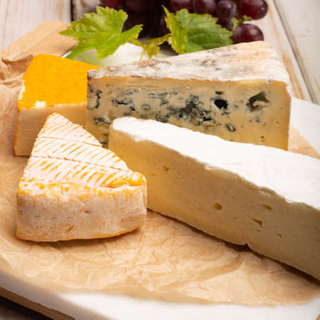 Tasting plate with four France cheeses, cream brie, marcaire, saint paulin and blue auvergne cheese, served with fresh ripe grapes close up