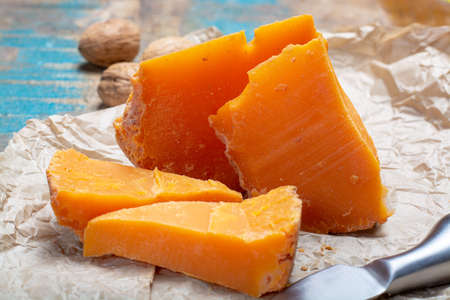 Pieces of native French aged cheese Mimolette, produced in Lille with greyish curst made by special cheese mites close up 스톡 콘텐츠