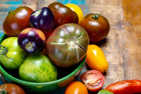 Multicolored assortment of French fresh ripe tomatoes on blue wooden table close up