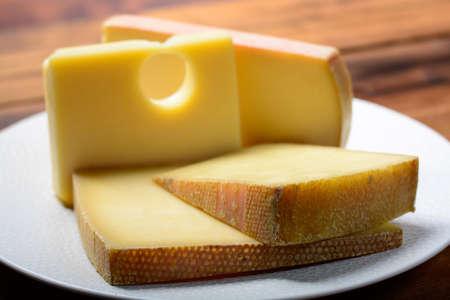 Schweizer Käsesortiment Emmentaler oder Emmentaler mittelharter Käse mit runden Löchern, Gruyere, Appenzeller und Raclette für traditionelles Käsefondue oder Gratin Standard-Bild