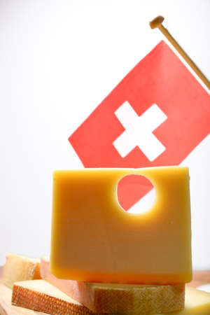 Block of Swiss Emmental or Emmentaler medium-hard cheese with round holes made from cow milk in Canton Bern with flaf of Switzerland