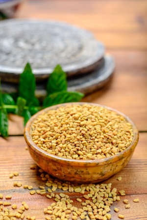 Bowl with fenugreek seeds close-up, used for cooking and traditinal medicine, spices collection