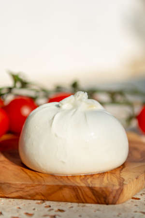 Fresh soft white burrata, buttery cheese, made from a mix of mozzarella and cream, original from Apulia region, Italy with tomatoes