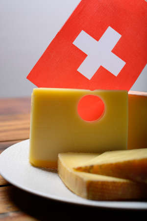 Assortment of Swiss cheeses Emmental or Emmentaler medium-hard cheese with round holes, Gruyere, appenzeller and raclette used for traditional cheese fondue and gratin and flag of Switzerland Stock Photo