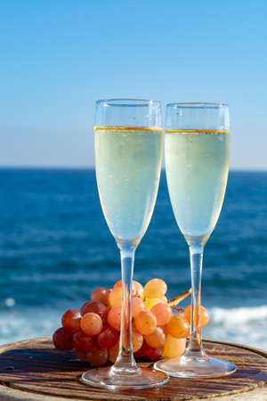 Champagne, prosecco or cava served with pink grape in two glasses on outside terrace with sea view close up