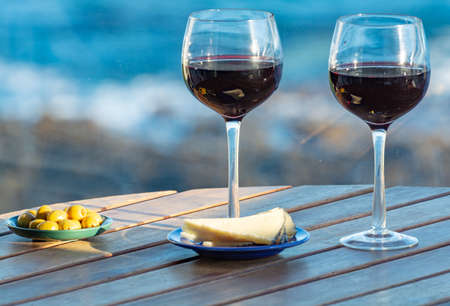 Aperitif, red wine in glasses served with cheese and olives on outdoor tessace witn sea view close up Stockfoto