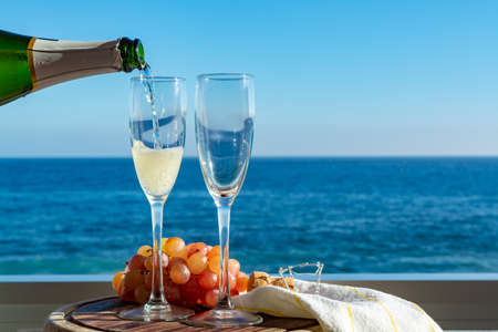 Waiter pouring Champagne, prosecco or cava in two glasses on outside terrace with sea view  close up Foto de archivo