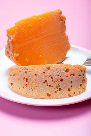 Two pieces of native French aged cheese Mimolette, produced in Lille with greyish curst made by special cheese mites close up