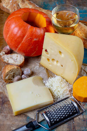 Ingrediens for traditional seasonal Swiss dish, pumpkin fondue with gruyer and emmentaler cheeses, white wine, fresh creme and bread close up Banque d'images