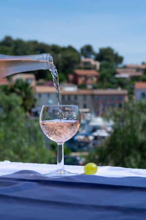 Waiter pouring cold rose wine on outdoor cafe terrace in sunny summer day in Provence, France