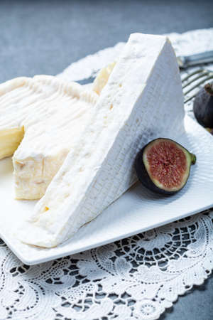 Two pieces of French soft cheeses Brie and Camembert with white mold and strong odor, served with fresh ripe figs close up